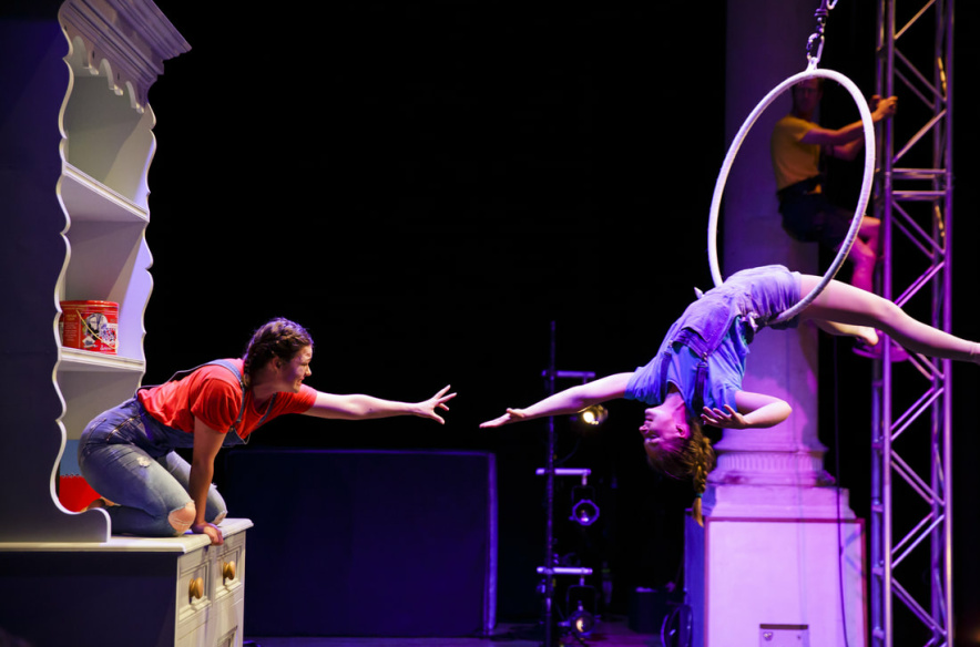 Two performers on stage, one of them is suspended on a hola-hoop and is reaching out to the other one who is sitting on an oversized cupboard.