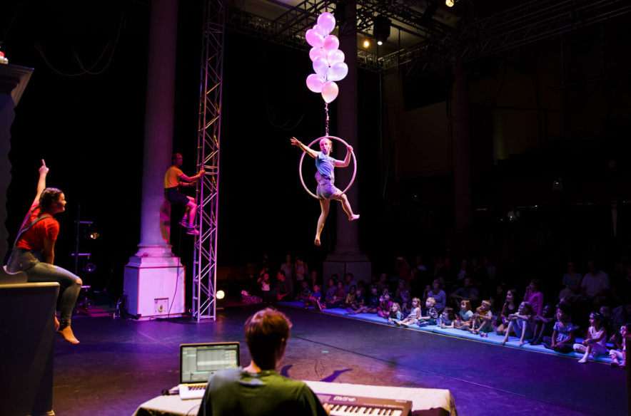 Four performers on stage, one of them is sat on a suspended hola-hoop with balloons attached to it - they look like they're floating in the air. A group of children is watching the performance, sitting by the edge of the stage.