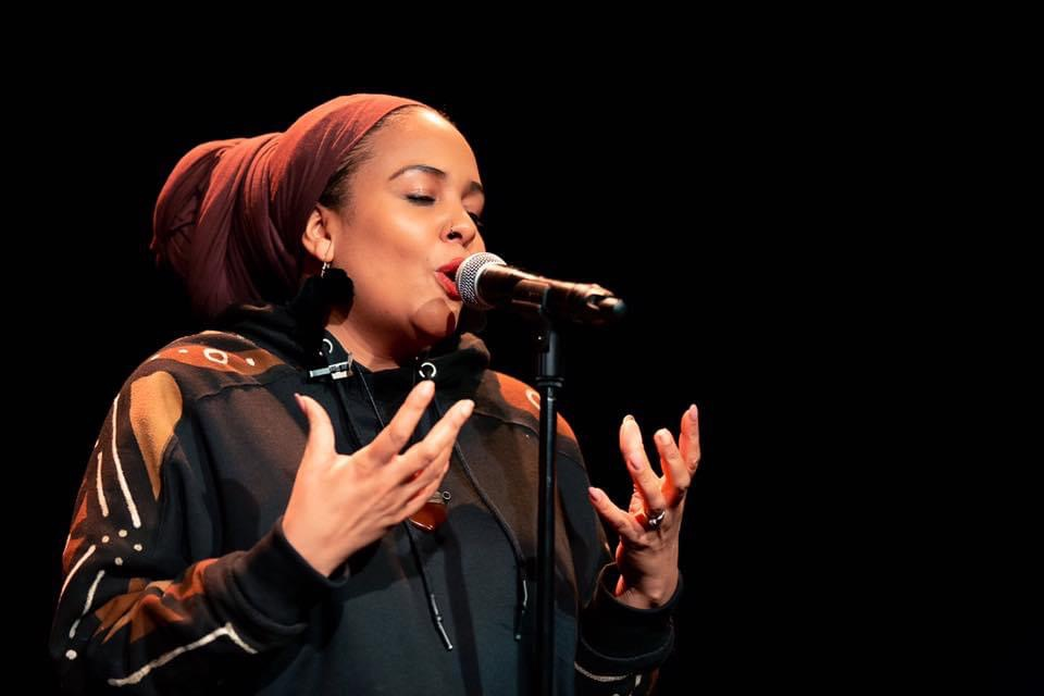 Sukina is singing or speaking animatedly to a microphone. She is a person of colour, she is wearing a brown headscarf and a black hoodie.