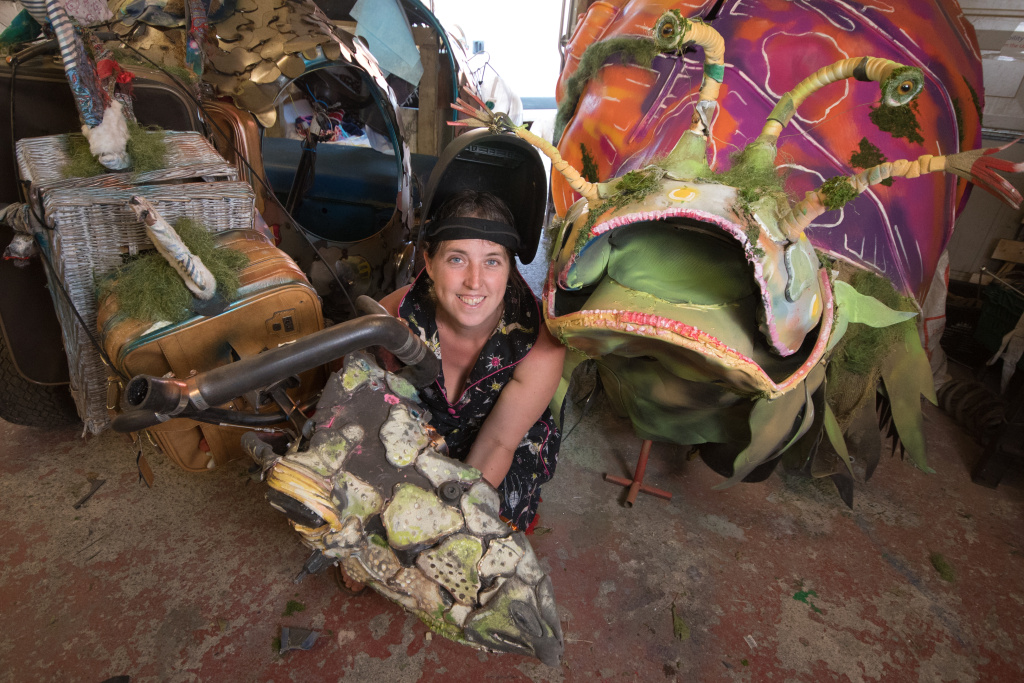 Ruby is squatting in a workshop, between two sculptures of grotesque, fantastique, dinosaur-like creatures. She is smiling and looking directly into the camera. Ruby is a white person with dark hair, she is wearing a welding mask on her head and a black dress, pattern with stars and starships.