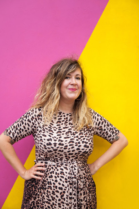 Amy is standing in front of the pink and yellow wall with her arms akimbo. She is looking directly into the camera and smiles. Amy is a white person with wavy, ombre-blond hair. She is wearing pink lipstick and a leopard-print dress with short sleeves.