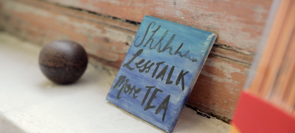"""A hand painted tile propped on a windowsill. The writing on it says """"Shhh, less talk, more tea"""""""