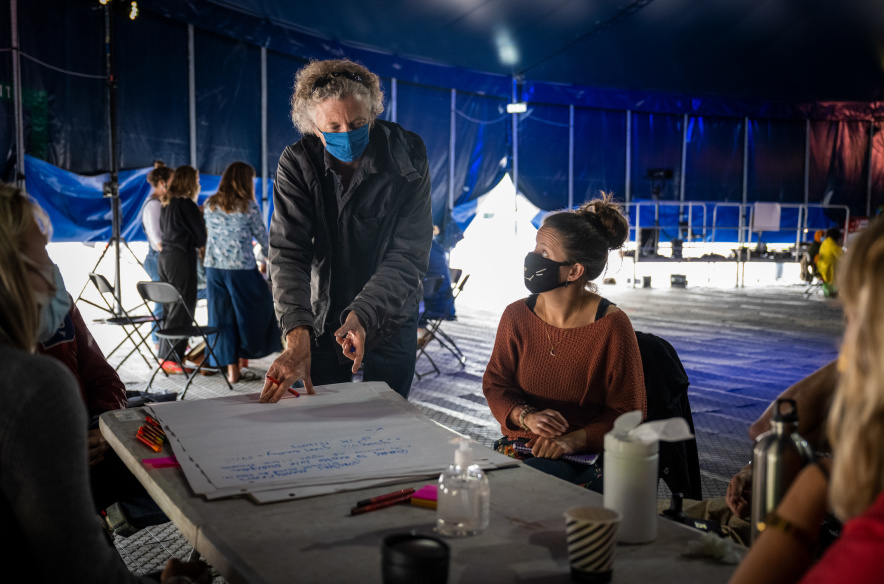 Participants are gathered around the table inside the blue, big top. The one whose face we see looks at the facilitator who is pointing to a flip chart on the table, ready to write something down.