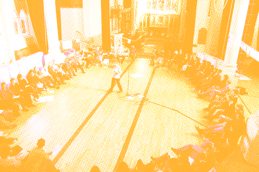 A yellow-tinted image of people sitting in the circle with the speaker in the middle of it.