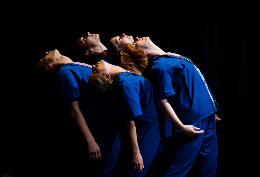 Five performers dressed in blue shirts and trousers, they are all bent backwards in the same direction.