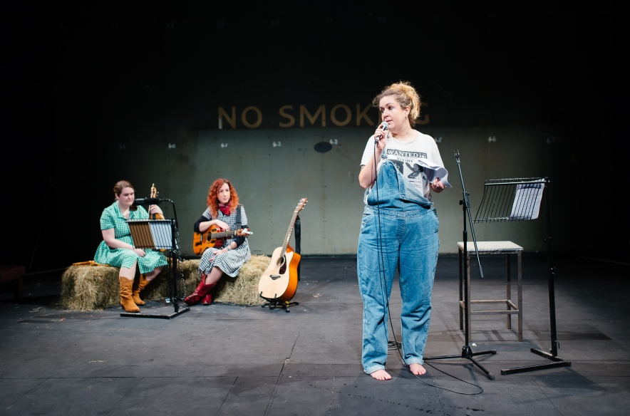 Amy is dressed in denim dungarees and speaks to the mic. At the back there are two performers sat on hay bundles with guitars and a music score. There is a no smoking writing at the back of the stage.