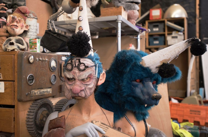 At the forefront there are two grotesque puppets, one is wearing an old-men's mask and holding a cardboard gun, the other is a blue bear. Both are wearing clown's hats and have female torso's. Behind them there are shelves full of props and materials.