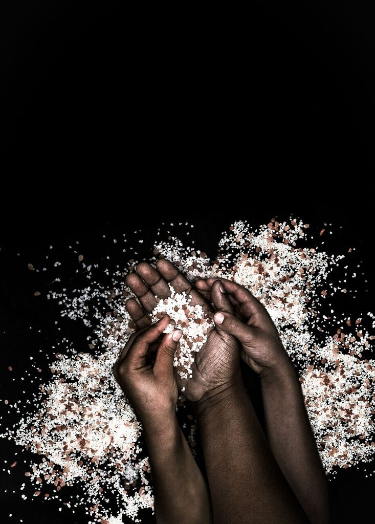A pair of black person's hands is picking up crumbs of salt from an open palm of another black person. There is a lot more salt scattered around the hands.