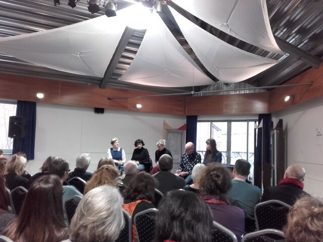 A panel discussion with 5 speakers and an audience sat on chairs.