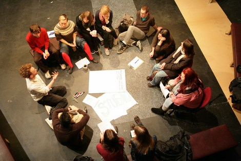 A birds-eye view of DIY meeting with 12 people sitting in a circle and discussing something. There are pieces of paper and markers on the floor.