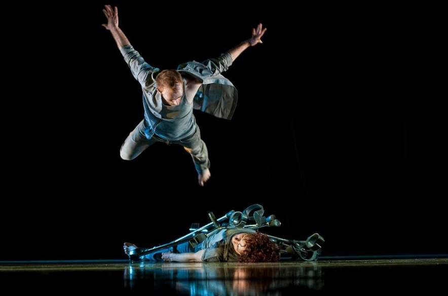 A performer covered in crotches is lying on the stage floor, a second performer is jumping above them.