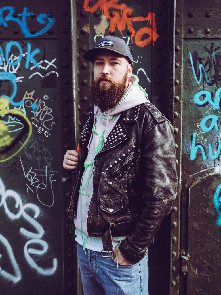 Mike is a white person with brown beard, they are wearing a baseball cap, leather jacked, grey hoodie and denim trousers. They are standing in front of the wall covered with graffiti.