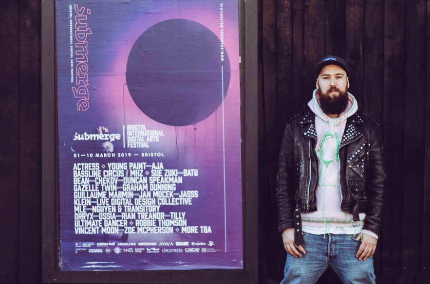 Mike is a white person with brown beard, they are wearing a baseball cap, leather jacked, grey hoodie and denim trousers. They are standing astride next to the Submerge festival poster.