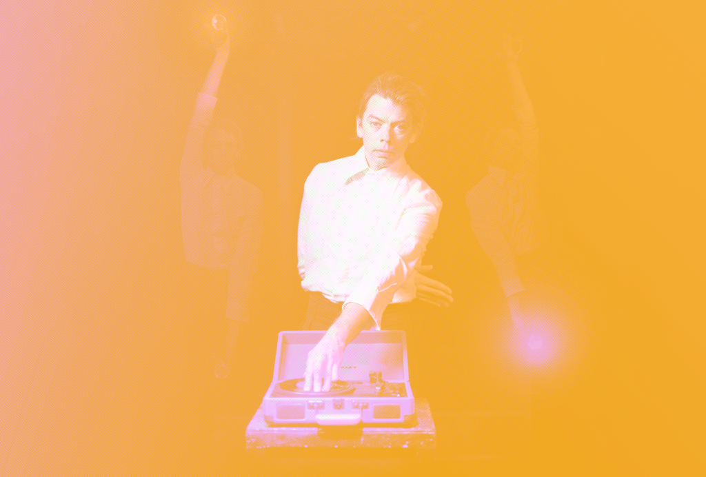 A yellow tinted image of Tom Marshman, he is wearing white shirt and is touching a record player.
