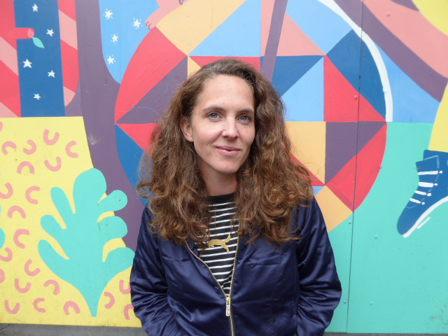 Kate is a white person with light brown hair, she is smiling and wearing a blue jacket. She stands agains the colourful mural.