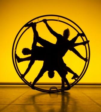 Three dark silhouettes inside a cyr wheel against the yellow background.