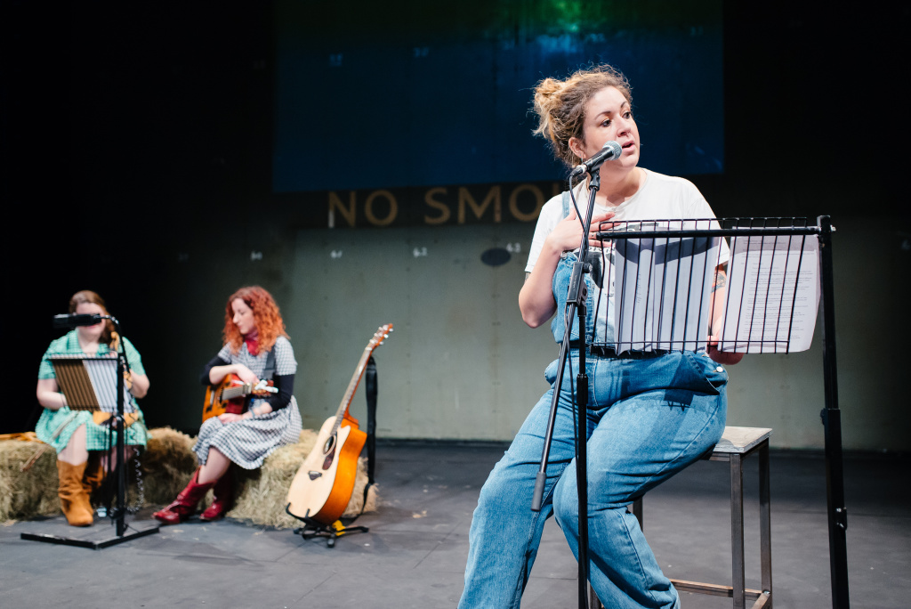 Amy is dressed in denim dungarees and performs from behind a score. At the back there are two performers sat on hay bundles with guitars and a music score. There is a no smoking writing at the back of the stage.