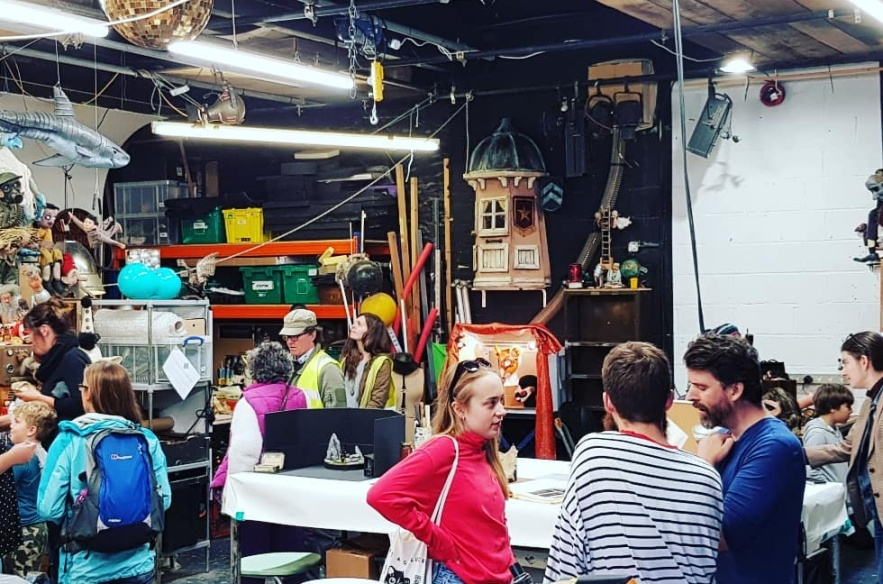 An inside of the puppetry warehouse with many people inside, chatting in small groups. The space is filled with props and materials and is lit with the strip lights. There is a gold disco ball hanging from the ceiling.