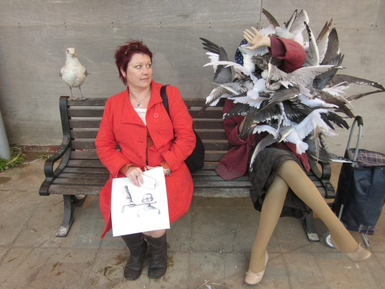 Ruth is a white person with short red hair, wearing a red coat and sat on a bench next to Banksy's sculpture of a women attacked by seagulls.