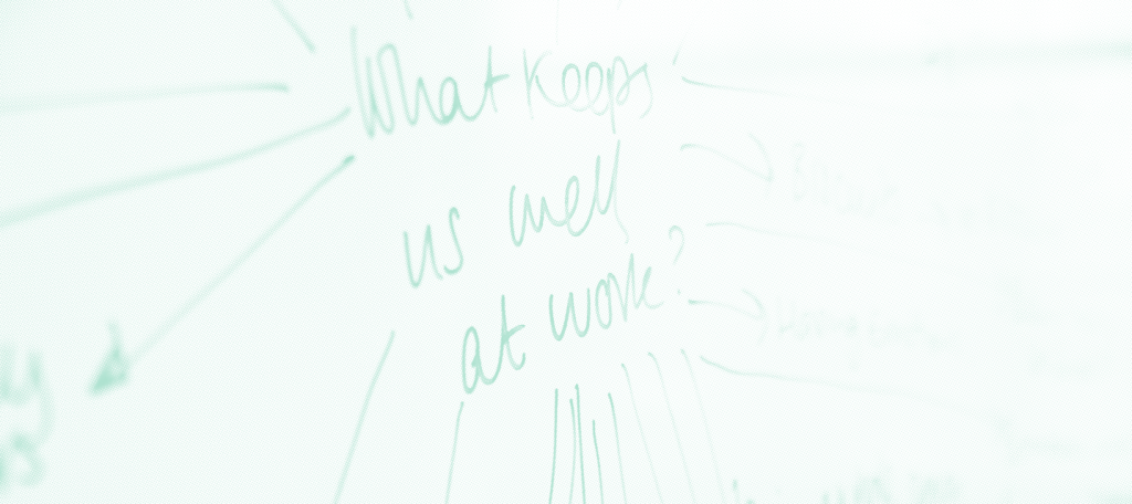 """A close-up of a whiteboard with writing that reads """"What keeps us well at work?"""""""
